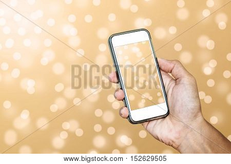 Hand using Smartphone taking a Photo of Defocus Gold Bokeh Lights Background