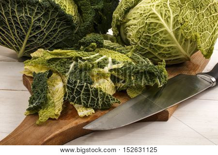 organic savoy cabbage is cut on a wooden board in small strips and prepared for cooking