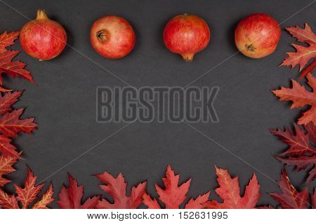 Pomegranates in a row and frame of autumn red fallen leaves on grey background