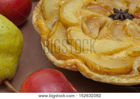 Tarte Tatin apple and pear tart pie on light brown background with copy space
