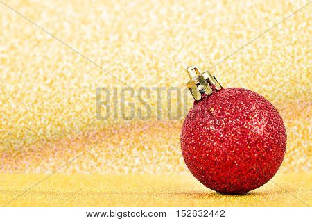 Red ball Christmas decoration on golden abstract background