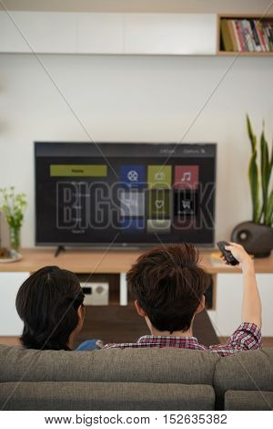 Man using remote control to choose channel, view from the back