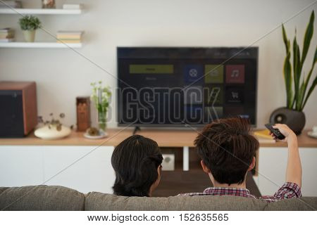 Couple watching tv shows on their smart tv at home