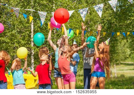 Big group of happy age-diverse kids playing balloons at outdoor birthday party