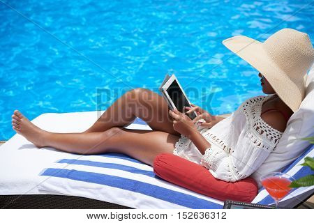 Young woman relaxing at pool with digital tablet
