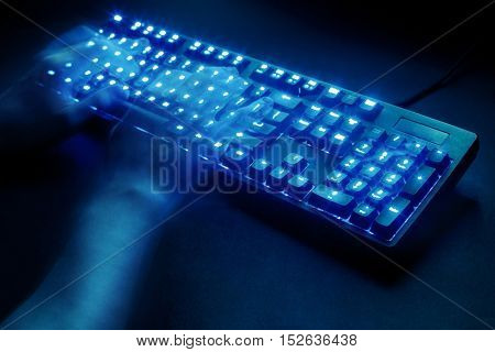 illuminated keyboard. male hands typing on a computer. hacker or programmer at work. on a black background. view from above.