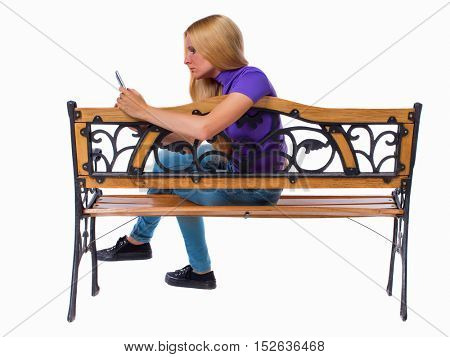 back view of woman sitting on bench and looks at the screen of the tablet.  Rear view people collection.  backside view of person.  Isolated over white background. Sad girl reads from the phone.