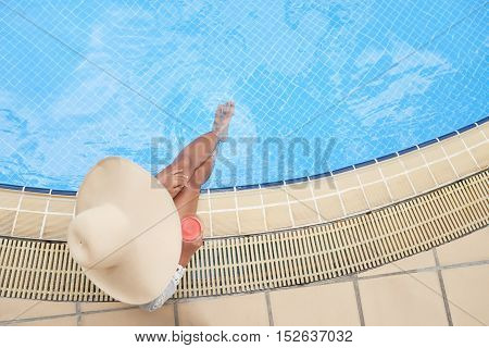 Woman in big hat sitting at pool with cocktail, view from above