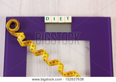 Tape measure on household digital bathroom scale for weight of human body concept of healthy lifestyle and slimming
