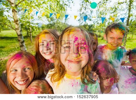 Close-up portrait of happy kids, boys and girls, with faces smeared with colored powder
