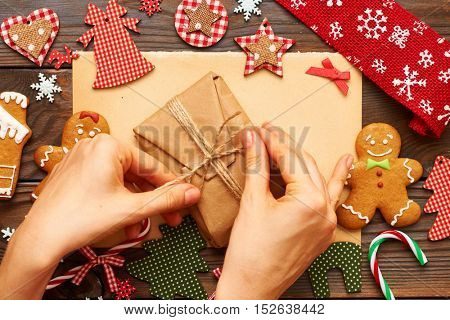 Female hands over christmas gift and homemade gingerbread cookie with handmade decoration on wooden background