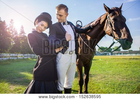 Multi ethnic couple dressed very formally are riding their horse in their stables