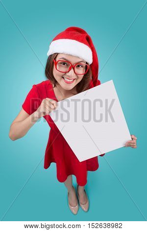 High view of smiling beautiful happy girl in christmas santa hat holding blank board on blue background.