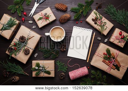 Gift or present box wrapped in kraft paper with christmas decoration cup of coffee and empty notebook on rustic wooden table from above. Flat lay style.