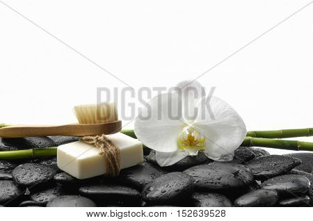 White orchid blossom with black stones ,grove ,soap,on wet background