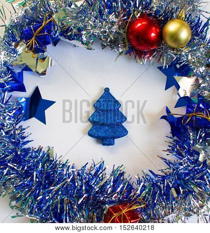 Christmas ornament in silver and blue on white background. New Year decoration flat lay. Shining and sparkling ribbon with fir tree toy inside. Blue sparkling firtree. New Year or Christmas picture