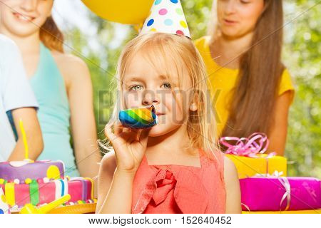Little adorable blond girl blowing a whistle at the outdoor birthday party