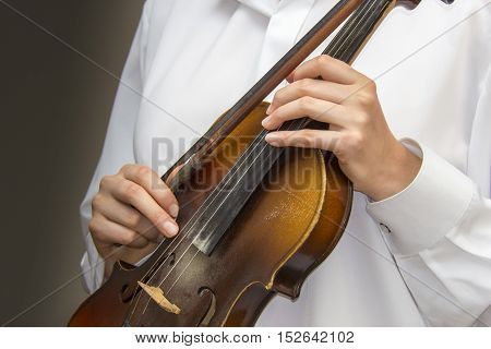 Close view of girl's hands on the strings of a violin