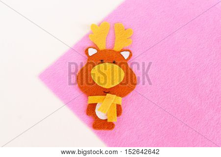 Felt deer set. Brown felt deer toy on pink background. Step