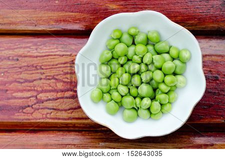 Fresh green peas on white plate close-up.