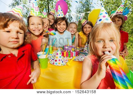 Happy age-diverse kids having fun with bright party whistles at the outdoor birthday party