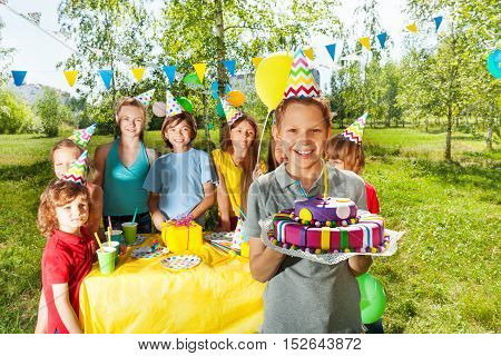 Portrait of happy young boy holding mastic icing birthday cake with burning candle stick on it