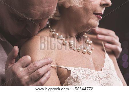 Senior Man Kissing Female Arm