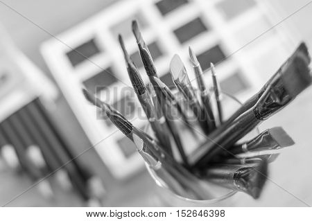 Paint brushes in glass on the table in a workshop. Master drawing at background.Close up.
