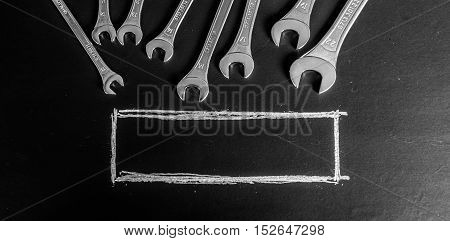 Black chalkboard with wrenches, service. Blackboard. Blank border for text.