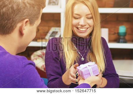 Young man making a gift to the girl. Romantic man and woman relationship.