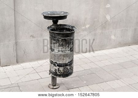 Old damaged dustbin in the street detail