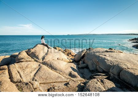 Woman sitting at the edge of the rock and looking into the sea at Port Elliot South Australia