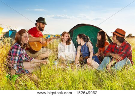Portrait of six happy young people singing to the guitar, sitting on the grass at campsite