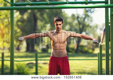 Well built muscular man doing a physical exercise outdoors