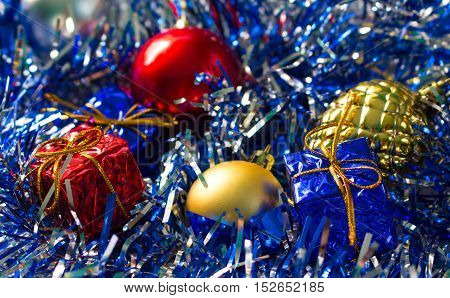 Christmas ornament background. Red and gold ball. Golden pine. Blue and red wrapped gifts. Sparkling ribbon with needles. Close-up photo for New Year greeting card seasonal holiday banner template