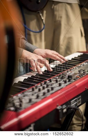 Hands of musician playing keyboard musical instrument synthesizer concert