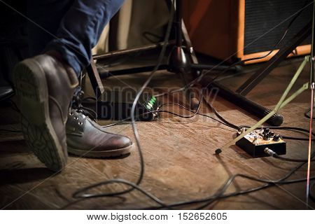 Feet of the musician on stage guitar processor column