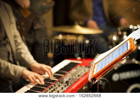 Music Band Playing In Concert, Musical Instruments, Tablet, Blurred Background