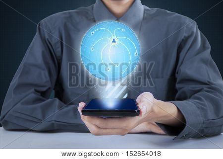 Close up of businessman holding modern smartphone while showing 3d earth globe with connection network