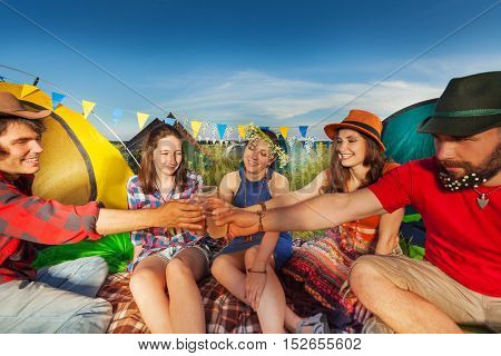 Portrait of five happy friends clanging glasses together at campsite