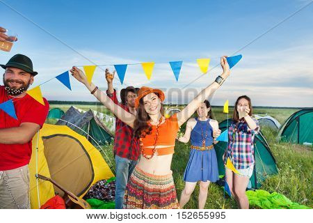 Company of four friends having fun, dancing and drinking at campsite festival at sunny day