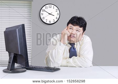 Image of overweight businessman using computer and daydreaming in the office
