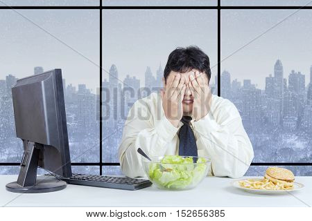 Overweight entrepreneur is refusing food and closing eyes while sitting in the office room with winter background on the window