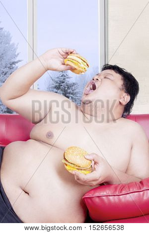 Portrait of an overweight man holding two hamburgers while sitting on the red couch in winter season