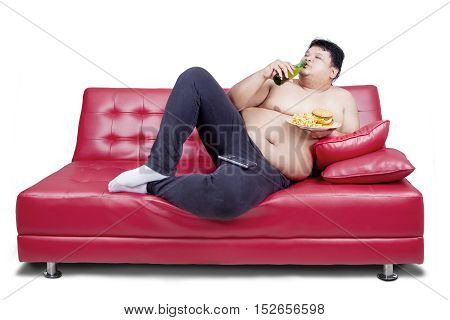 Overweight man reclining on couch and holding junk food while drinking fresh beer with watching tv isolated on white the background