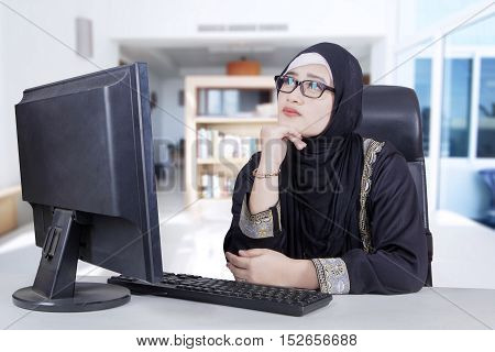 Arabian businesswoman wearing glasses sitting in the living room while daydreaming with computer