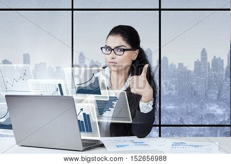 Young entrepreneur sitting in front of virtual chart on the laptop while showing thumb up at camera with winter background on the window