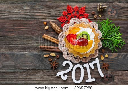 Christmas and New Year 2017 background with fruit tart and decorations - snowflake crochet napkin pine cones. Place for text.