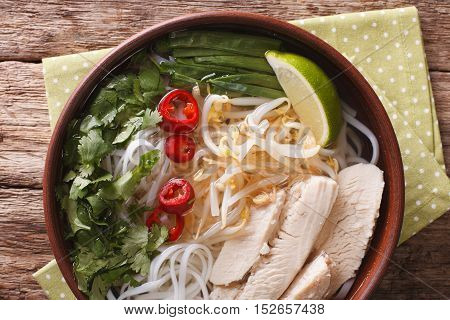 Vietnamese Food: Spicy Soup Pho Ga With Chicken, Rice Noodles And Herbs Close-up. Horizontal Top Vie