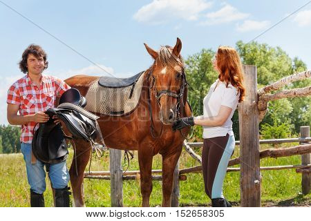 Two happy horseback riders, young man and woman saddling bay horse standing next to the enclosure fence